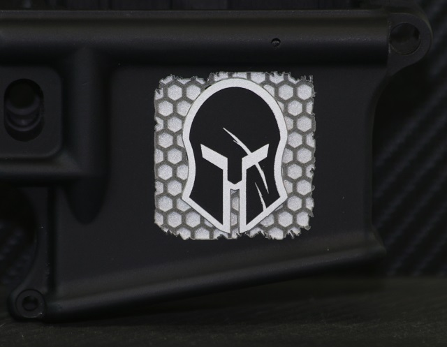 laser engraved ar15 lower receiver with enhanced 3d engraving style spartan helmet and hex background pattern